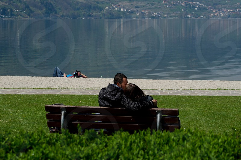 couple kissing each other on a park bench photo