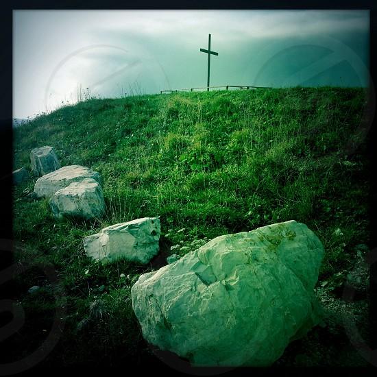 white rocks green grass field and black cross view photo