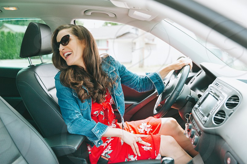 A beautiful woman in a car smiling at someone in the back seat.  photo