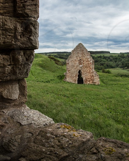 Scottish countryside and stone stable ruins as seen from a castle window photo
