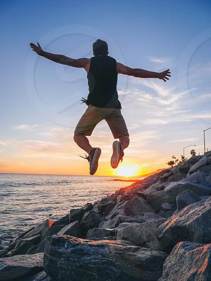 man in black tank top jumping photo