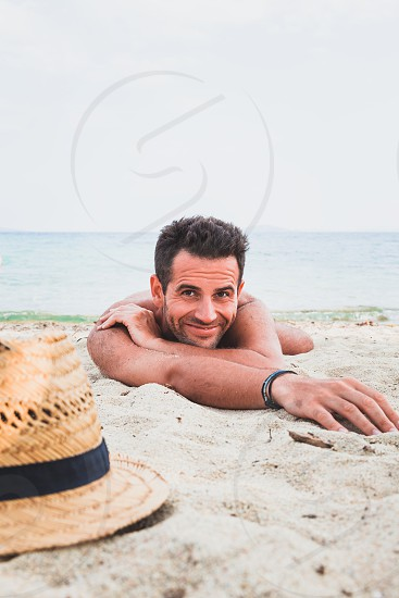 Young man on the beach lying in the sand photo