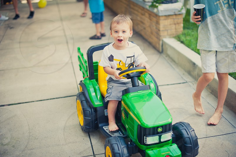 boy in white shirt riding on cart toy photo
