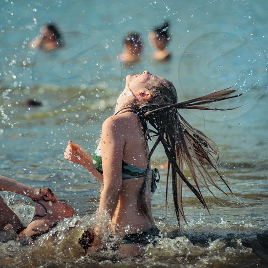 Girls have fun jumping in water and make splah with long hairs photo