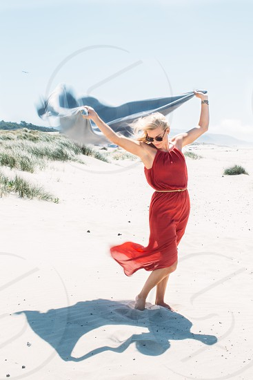 woman wearing red chiffon halter dress holding blue textile standing on white sand over blue sky during daytime photo