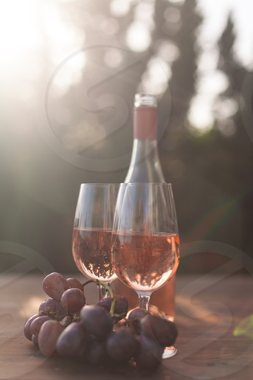two wine glasses filled with rose wine next to the wine bottle and purple table grapes under the sun photo