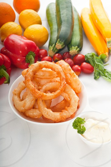 golden deep fried onion rings served with mayonnaise dip  and fresh vegetables oln background MORE DELICIOUS FOOD ON PORTFOLIO photo