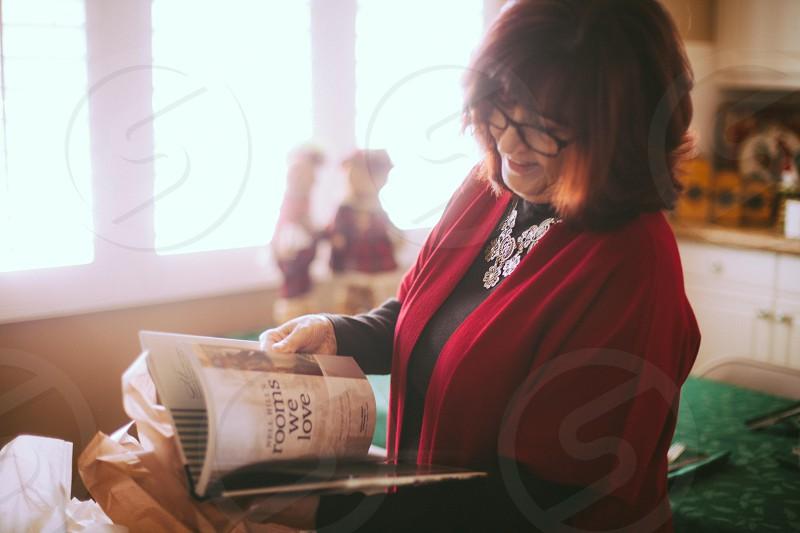 woman wearing black blouse reading a magazine photo