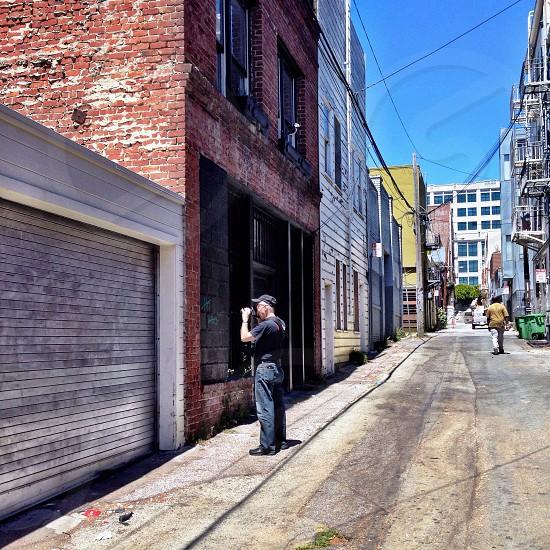 alley with man wearing black baseball cap and black short sleeve shirt photo