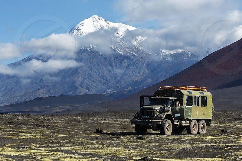 TOLBACHIK VOLCANO KAMCHATKA RUSSIA - AUG 27 2014: Russian off-road extreme expedition truck ZIL-131 (6-wheel drive) on mountain road on volcanic slag field on background of beautiful volcano. Russia Kamchatka Klyuchevskaya Group of Volcanoes. photo