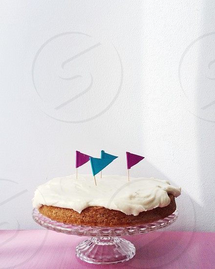 white cream topping on brown round cake on clear glass round cake tray photo