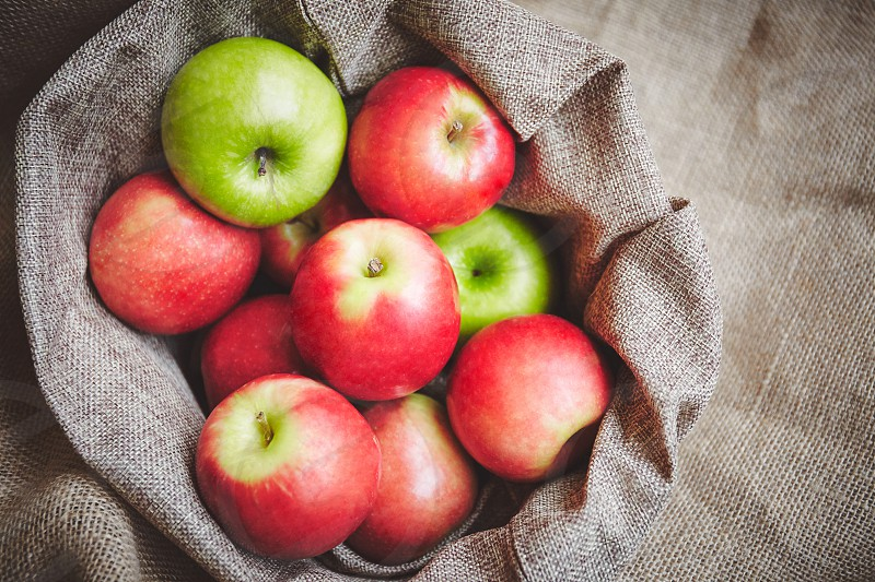 Top view red apples green apples in basket cover with brown cloth background texture photo