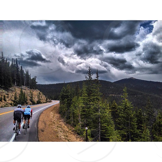 two cyclists on road during cloudy day photo