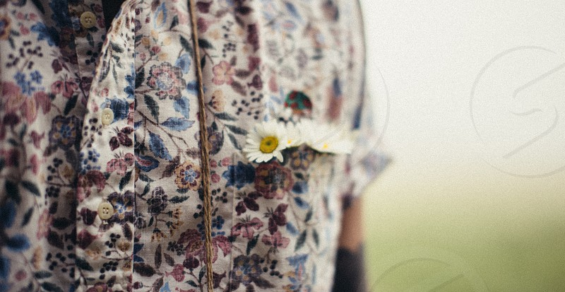 selective focus photo of white petaled flowers stuck on white pink and blue floral button up shirt side pocket photo