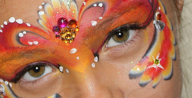 Close-up of a girl's eyes and her face which has elaborate face painting. photo