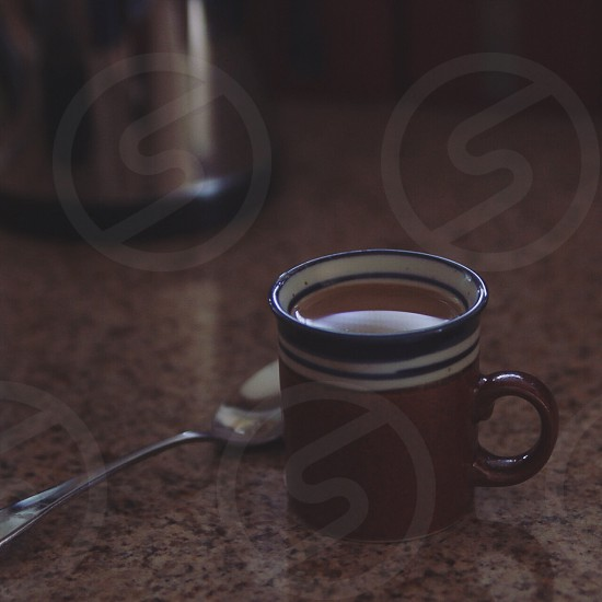 white blue brown ceramic mug with brown liquid almost full photo