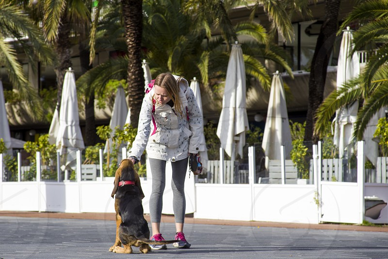 A girl in sports clothes on a walk with a bloodhound puppy photo