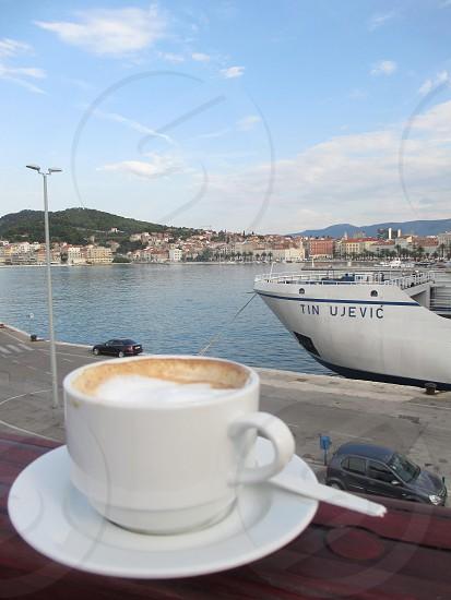 coffee ledge passenger boat cityscape water city dock calm anticipation voyage photo