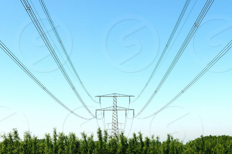 Electricity pylon with pwer lines and blue sky photo