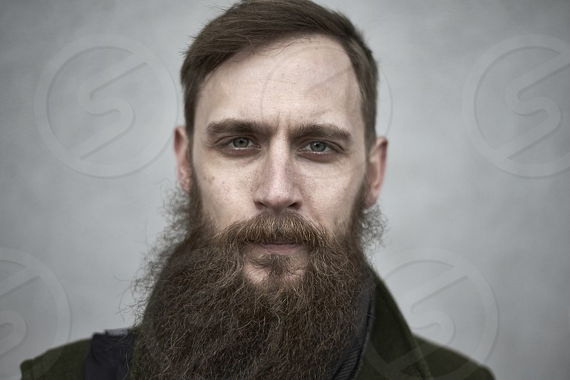 Portrait of a young man with a long beard shot outdoors in Copenhagen city centre photo