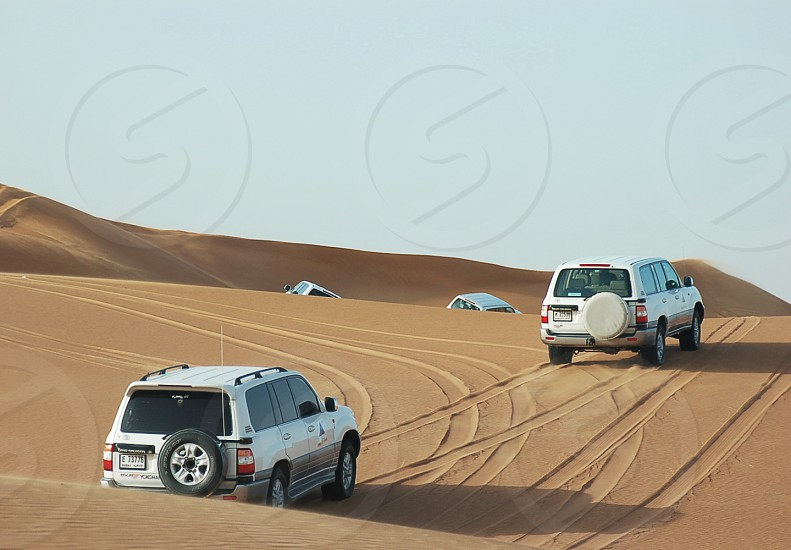 white suvs in sand photo