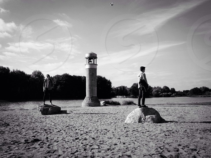 two people standing on rocks on a beach with a light tower surrounded by trees grayscale photo photo