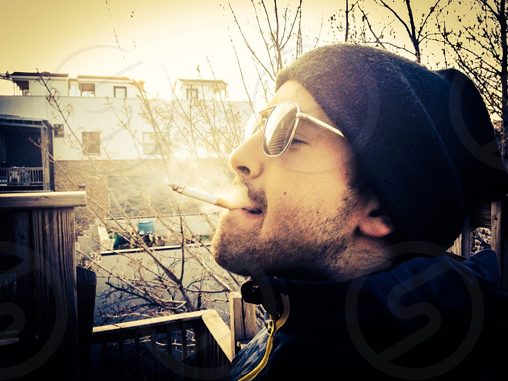 man in black zip up jacket and beanie smoking photo