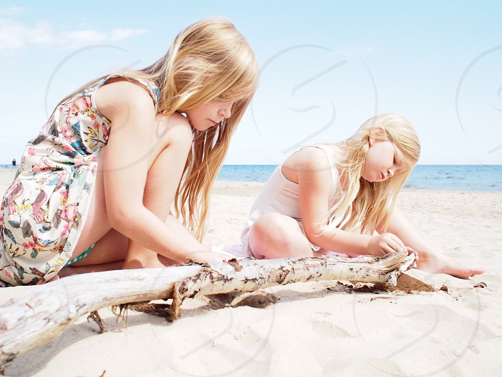 two young girls sitting on beach pulling bark from driftwood branch photo