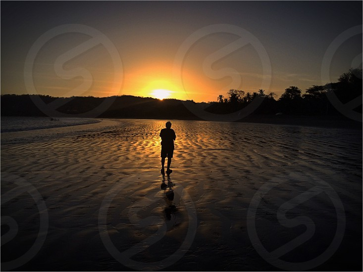 man walking in water silhouette  photo