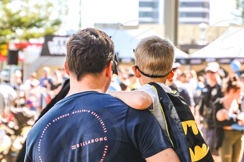 father and son enjoying a day out together little boy wearing Batman cape festival in the city photo