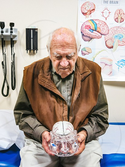 Alzheimer/dementia patient looking at the brain model in neurology waiting room. photo