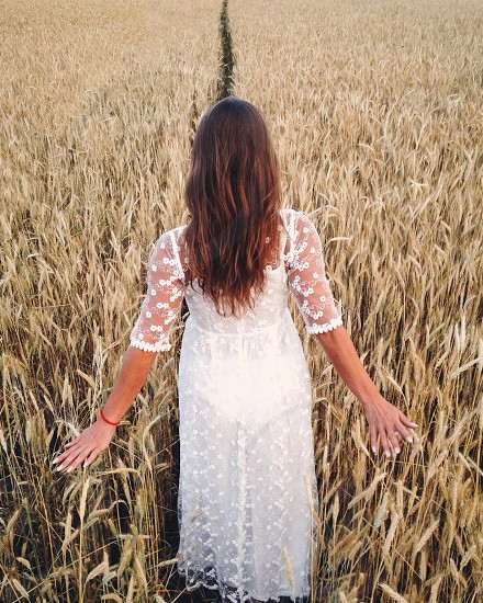woman in white floral lace mesh 3/4 sleeve dress standing between brown grass field photo