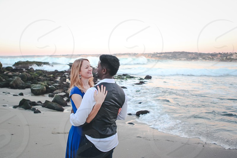 man wearing white dress shirt and black waistcoat hugging woman wearing blue short sleeve dress looking face to face at the shore photo