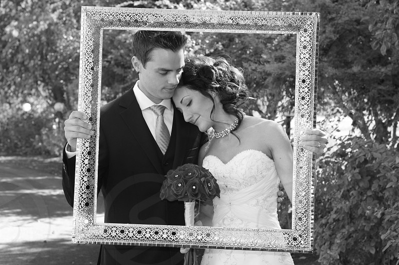 bride and groom holding a photo frame photo