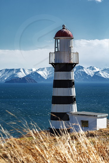 Petropavlovsky Lighthouse (founded in 1850) - oldest lighthouse in Russian Far East located on Cape Mayachny on Kamchatka Peninsula on shore of Avacha Gulf in Pacific Ocean in vicinity of Petropavlovsk-Kamchatsky City. photo