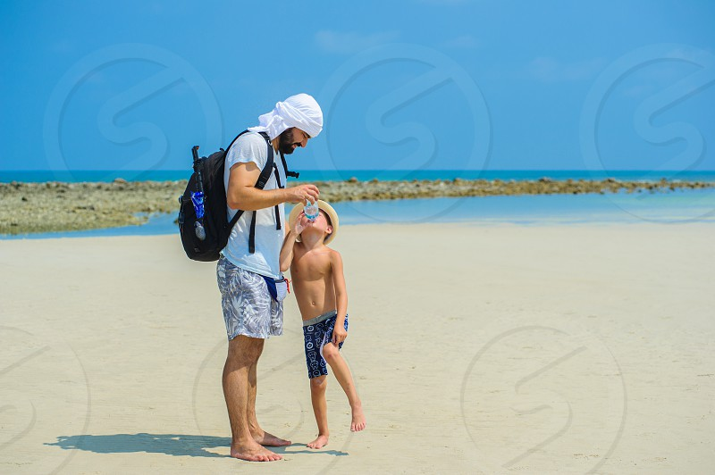 Father and son in the middle of the sandy beach quench their thirst. Only couple of water drops left in the bottle photo