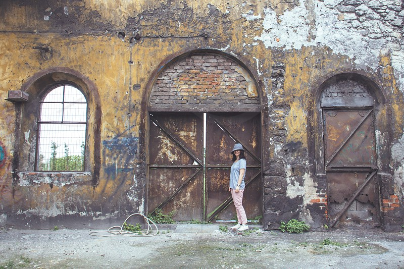 woman in gray crew neck t shirt wearing white pants and gray bowler hat beside brown wooden side by side doors photo