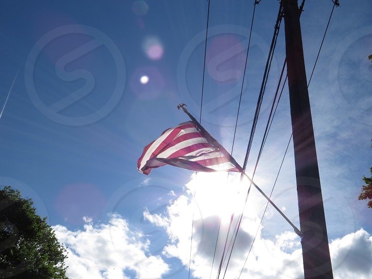 American flag Stars and Stripes sun blue sky  photo