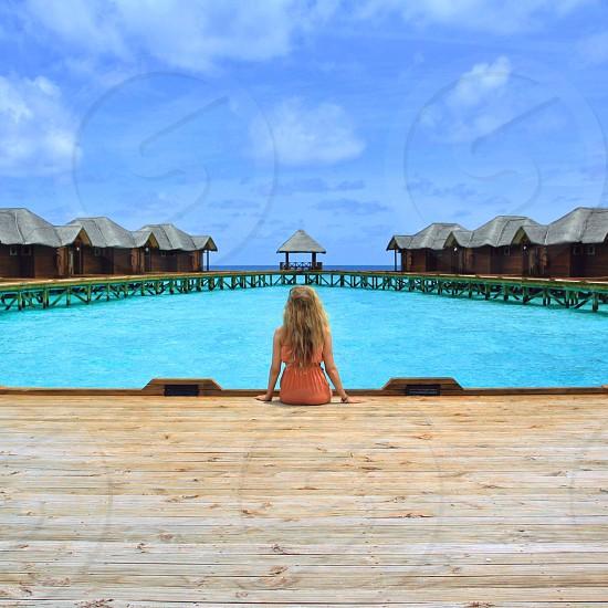 woman sittin on wooden dock photo