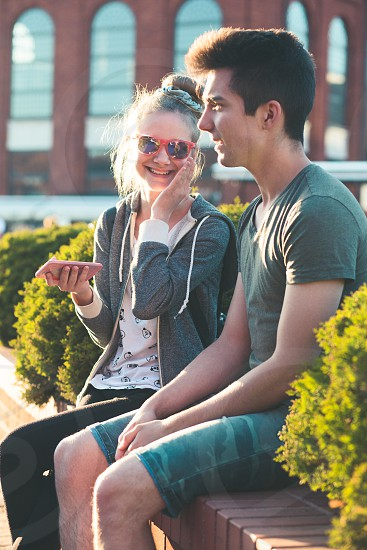 Couple of friends teenage girl and boy  having fun together with smartphones  sitting in center of town spending time together photo