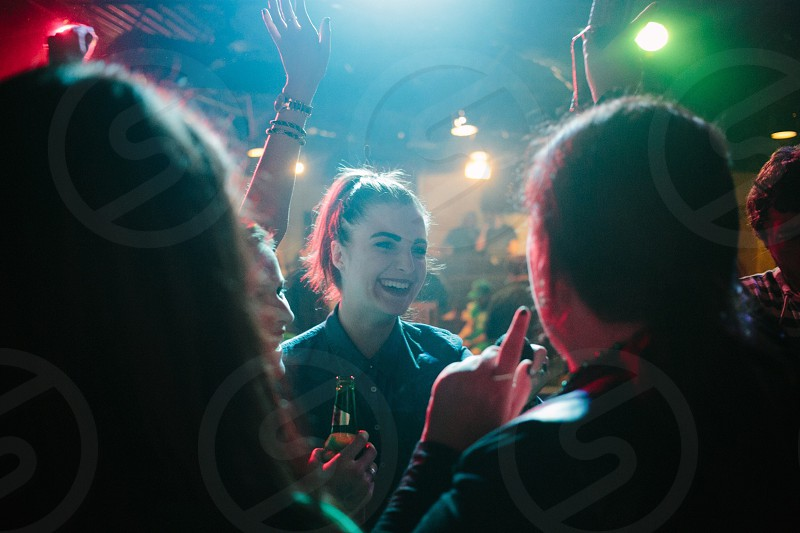 woman with red hair in pony tail smiling wearing denim collared shirt in club photo