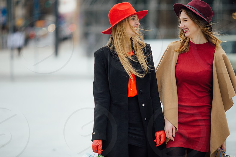 two women with hats walking photo