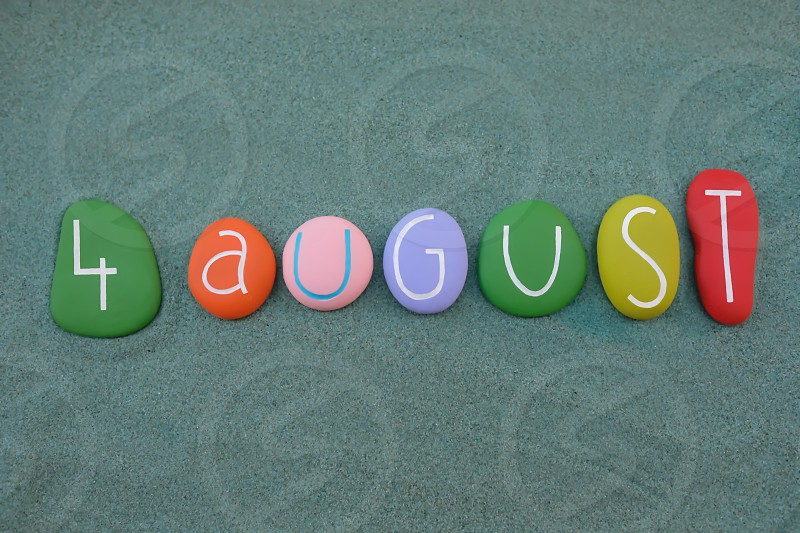 4 August calendar date composed with multi colored stones design over green sand photo