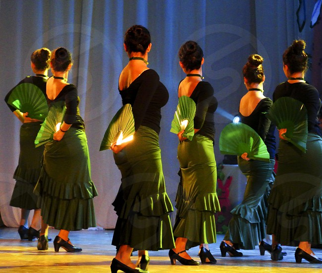 six women with black-and-green dresses dancing while holding hand fans with their right hand in their backs photo
