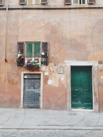 brown exterior wall with green wooden door photo