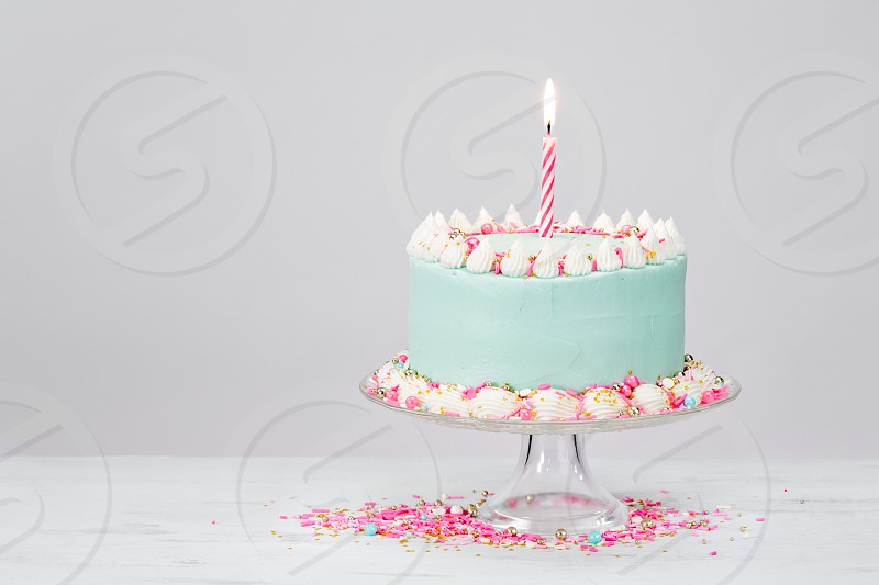 Pastel blue birthday cake over white background with pink sprinkles. photo