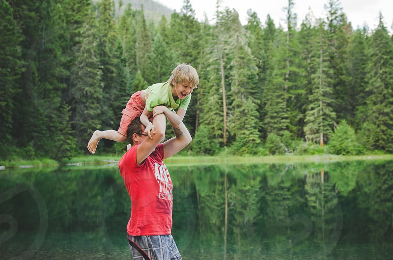 Dad throwing laughing child into a lake. photo