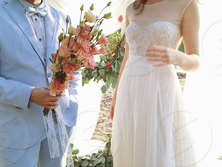 man in blue formal suit jacket holding pink and white flower near woman in white illusion neckline sleeveless gown during daytime photo