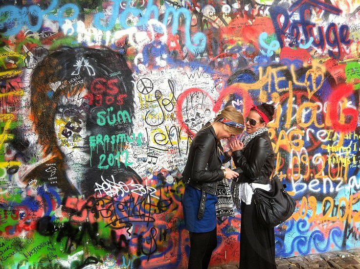 view of people standing beside graffiti wall photo