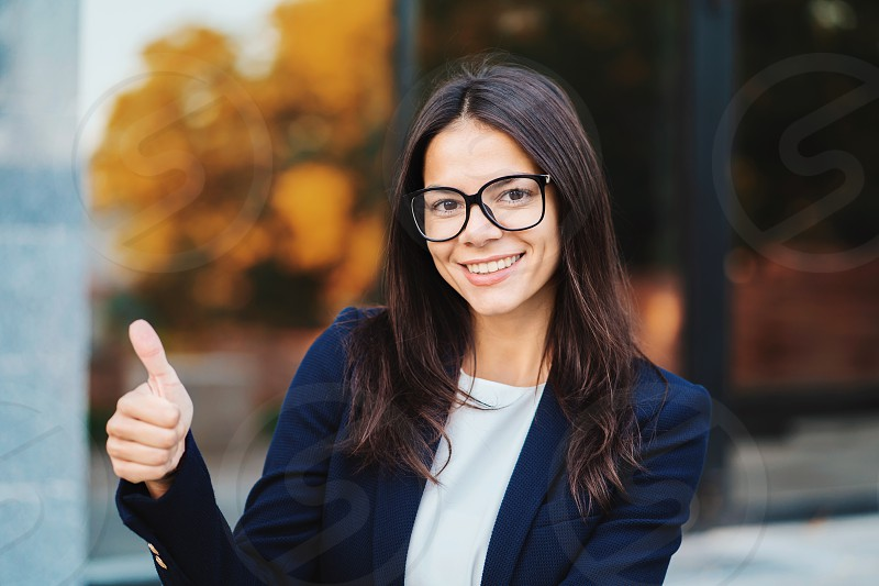 Portrait of young successful businesswoman wearing glasses and looking to camera professional female manager in corporate suit. Student girl wage worker weekdays concept photo